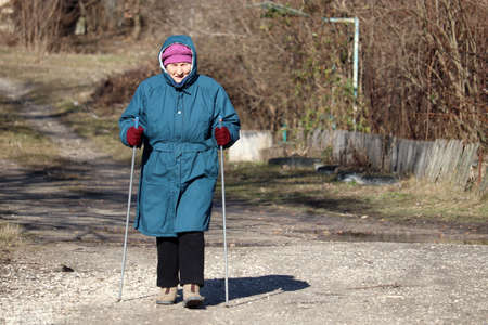 Elderly woman walking with sticks on rural road, sports exercises for healthy spine and joints. Nordic walking at cold weather, therapy for health