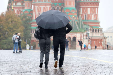 Rain in a Moscow, couple in autumn clothes with one umbrella walking on the Red Square on background of St. Basil's Cathedral. People in rainy weather, fall season