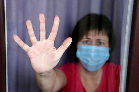 Quarantine during the covid-19 coronavirus epidemic, female palm of hand on the window. Worried woman in a medical face mask looks through the glass, plea of help