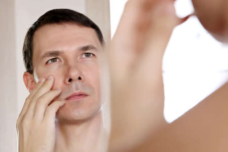 Handsome man looks at his reflection in the mirror touching his face. Male beauty, health and skin care concept