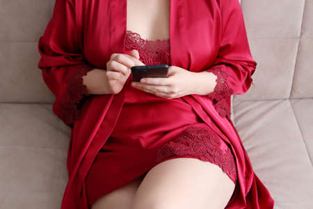 Smartphone in female hands, woman in red lace negligee sitting on a bed and using mobile phone. Concept of online addiction, sms or flirting