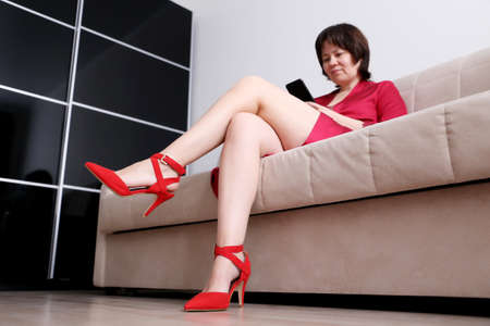 Woman in red shoes on high heels sitting on a sofa and using smartphone. Concept of online addiction, sms or flirting
