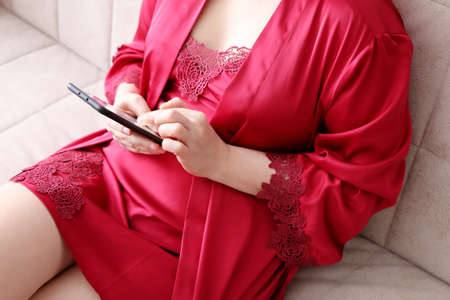 Smartphone in female hands, woman in red lace negligee sitting on a sofa and using mobile phone. Concept of online addiction, sms or flirting Standard-Bild