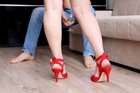 Love couple before at home. Woman in red shoes on high heels standing in front of man in jeans sitting with glass of white wine on sofa