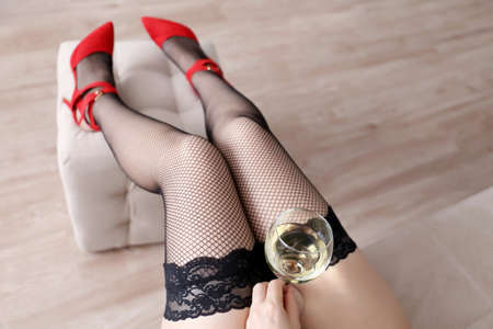 Woman in black fishnet stockings sitting with a glass of white wine. Drunk hot girl, concept of celebration, home relax, romantic date