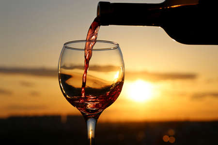 Red wine pouring from a bottle into the glass on beautiful sunset background. Concept of celebration, summer party at resort, romantic dinner outdoor