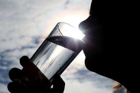 Person drinks clean water at sunshine background. Silhouette of woman enjoying beverage 版權商用圖片
