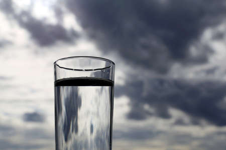 Drinking glass with clean water on background of dark sky with storm clouds