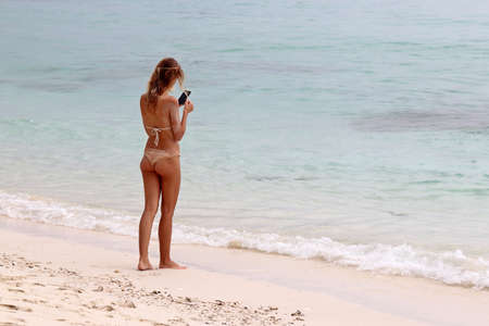Tanned slim girl in bikini standing on sandy beach with smartphone in hands. Sea vacation, using mobile phone in travel