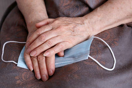 Wrinkled hands of elderly woman with medical face mask. protection for old people