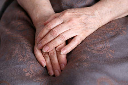 Wrinkled hands of elderly woman folded in her lap covered by headscarf. Life of old people