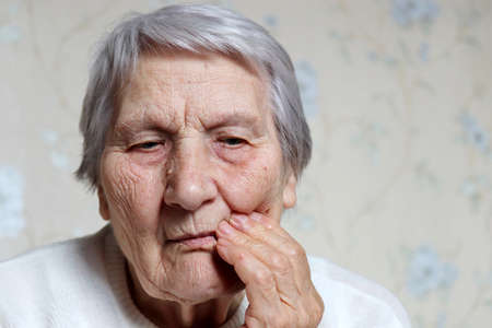 Elderly woman holding her cheek, female with gray hair suffering from a toothache. Concept of tooth pain, gum disease and old age