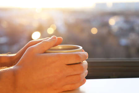 Fresh start in the morning, male hands with cup on sunrise background. Cozy atmosphere, city view from the window
