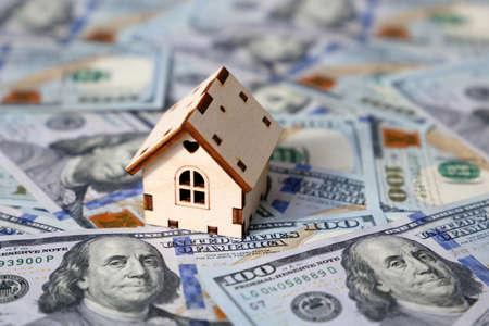 Wooden house model on background of US dollars banknotes. Housing market, purchase or rental of real estate