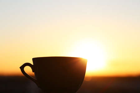 Silhouette of coffee cup on sunrise background, fresh start in the morning. Cozy atmosphere, city view from the window 版權商用圖片