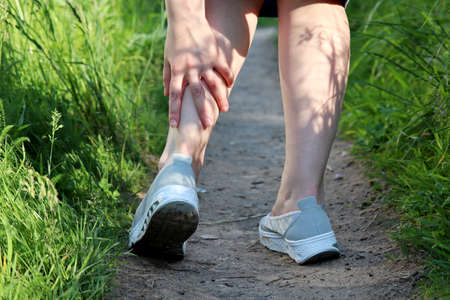 Ankle sprain, woman grabbed her leg while walking on a spring or summer nature. Concept of tired legs, injury on running