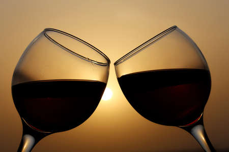 Two glasses with red wine on sunset background, evening sun is reflected in a glass. Concept of celebration, romantic cocktail, love date, wine tasting