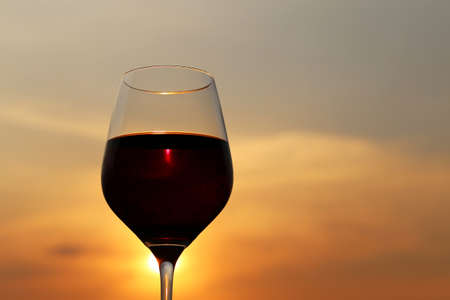 Glass with red wine on sunset background, evening sun is shining through the glass. Concept of celebration, wine industry