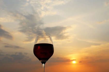 Glass with red wine on sunset background, evening sun and colorful sky are reflected in a glass. Concept of celebration, wine industry