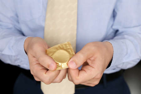 Condom in male hands close up, safe sex. Man in office clothes using contraceptive, contraception at work concept