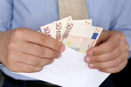 Euro banknotes in male hands close up, man in business clothes with money in white envelope. Concept of cash, income, bribe or salary