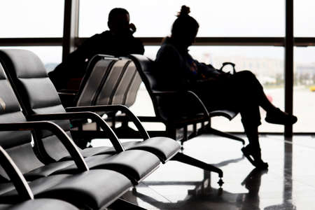 Passengers in the airport, defocused silhouettes of man and woman sitting against the window. Travelers waiting flight