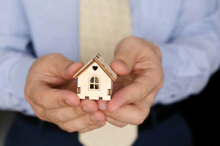 Real estate agent, wooden house in male hands. Man in office clothes with house model, purchase or rental home
