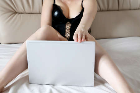 Hot woman sitting with laptop in a bed. Concept of working on a computer at home, internet web model, adult video chat