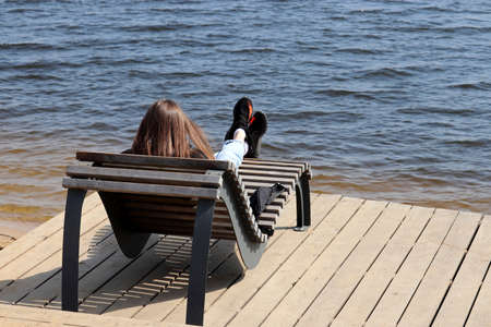 Girl in jeans lying on a wooden sunbed on spring beach. Leisure at cold weather near the water