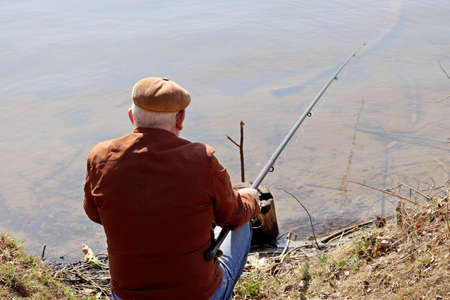 Fisherman sitting near the water with a fishing rod, rear view. Old man angling on the river coast at spring