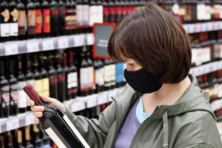 Woman in medical face mask reading the label on red wine bottle. Customer in liquor store, concept of choosing and buying alcohol