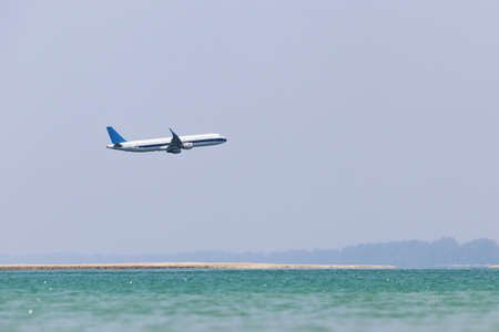 Airplane flies over the sea and sandy beach in mist. Summer vacation and travel concept 版權商用圖片