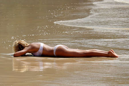 Sexy tanned woman with curly hair laying on a belly on a sandy beach in a waves. Concept of relax and leisure by the sea, fatigue after swimming, holiday and vacation