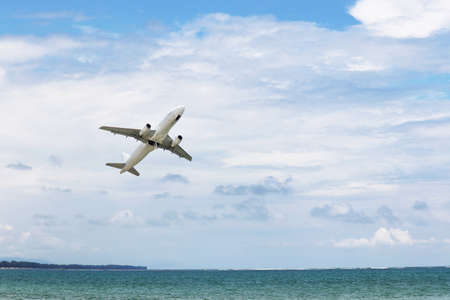 Airplane flies over the sea and coast on white clouds background. Commercial plane taking off and gaining altitude, vacation and travel concept 版權商用圖片