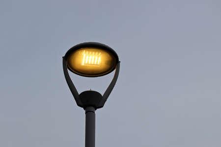 Glowing led lamp on sky background. Electric lighting, energy-saving street lantern