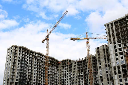 Construction cranes above unfinished residential buildings on blue sky and white clouds background. Housing construction, apartment block in city 版權商用圖片