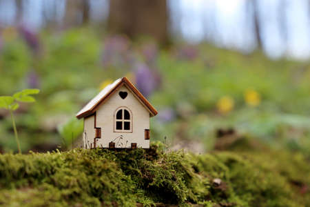 Wooden house model in a forest on spring flowers background. Concept of country cottage, real estate in ecologically clean area, vivid colors of fairy nature 版權商用圖片