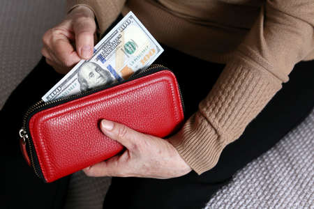 Elderly woman takes out US dollars from her red wallet. Concept of pension payments in USA, financial assistance, pensioner with money