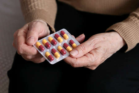Elderly woman with pills in wrinkled hands. Medication in capsules, taking sedatives, antibiotics or vitamins