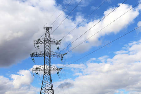 High voltage tower with electrical wires on background of blue sky with white clouds. Electricity transmission lines, power supply concept 版權商用圖片