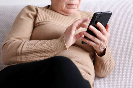Elderly woman with smartphone sitting on sofa at home, mobile phone in female hands. Concept of online communication in retirement, sms, social media