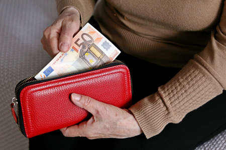 Elderly woman takes out a euro note from her wallet. Concept of pension payments, savings at retirement, pensioner with money