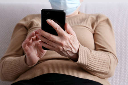 Elderly woman in face mask with smartphone sitting on sofa at home, mobile phone in female hands. Concept of online communication during quarantine, sms, social media
