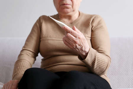 Elderly woman measuring body temperature, concept of fever, symptoms. Digital thermometer in wrinkled female hands