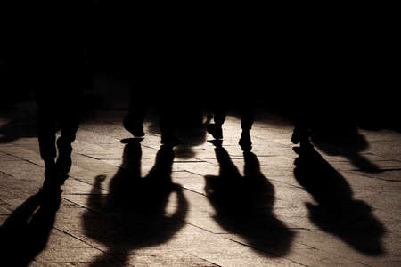 Black shadows and silhouettes of people on the street. Crowd walking down on sidewalk, concept of pedestrians, crime, society, population Stock Photo