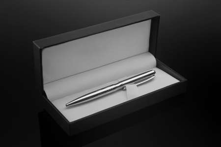Men's ballpoint pen in a gift case on a dark background. Concept.