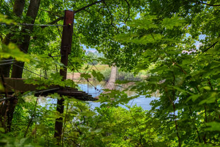Suspended wooden bridge across the river to the other Bank, through green leaves on a cloudy summer day. View of a wooden suspension bridge stretching into the distance