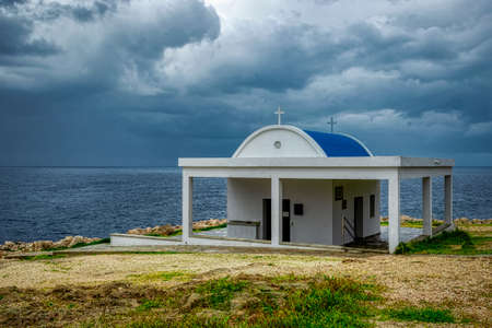 Cyprus, the Mediterranean coast. Church of Agia Anargiri on Cape Greco against the background of a summer storm sky Editorial