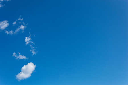 Bright blue sky with white clouds scattered on a natural background