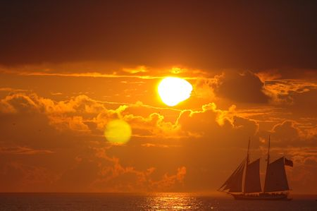 dramatic  sunset water clouds sail  photo
